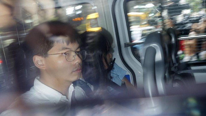 Pro-democracy activists Joshua Wong, left, and Agnes Chow, are escorted in a police van at a district court in Hong Kong, Friday, Aug. 30, 2019. Hong Kong police arrested well-known activist Wong and Chow, another core member of a pro-democracy group, Friday, and authorities denied permission for a major march in what appears to a harder line on this summer's protests. (AP Photo/Kin Cheung)