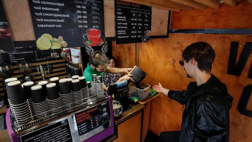CEO merek kacamata OCHIS COFFEE, Maksym Havrylenko mengambil ampas kopi di sebuah kafe di Kiev untuk dibuat menjadi kacamata. (REUTERS/Gleb Garanich)