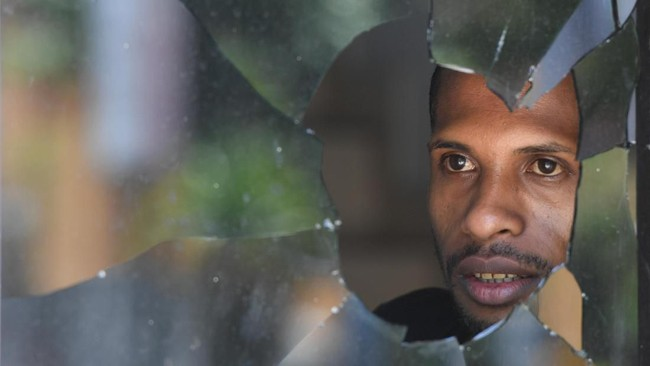 Warga melihat di balik kaca jendela yang pecah di Jayapura, Papua, Sabtu (31/8). Pada hari ini, kerusuhan telah mereda dan Kabid Humas Polda Papua mengatakan situasi kota kondusif. (ANTARA FOTO/Zabur Karuru)