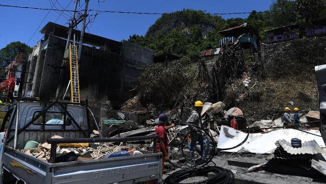 Petugas menata sambungan listrik yang rusak di salah satu rumah warga yang terbakar di Jayapura, Papua, Sabtu (31/8). Setelah dua hari dalam situasi mencekam, saat ini penduduk Jayapura mulai membenahi kota. (ANTARA FOTO/Zabur Karuru)