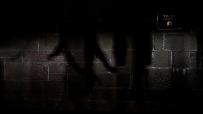 Bayangan seorang pejalan terlihat di tembok gereja Trinity di Manhattan, New York. Selain melakukan pekerjaan kasar, pada budak juga diperbantukan oleh para pengrajin yang memperindah bangunan. (REUTERS/Carlos Barria)