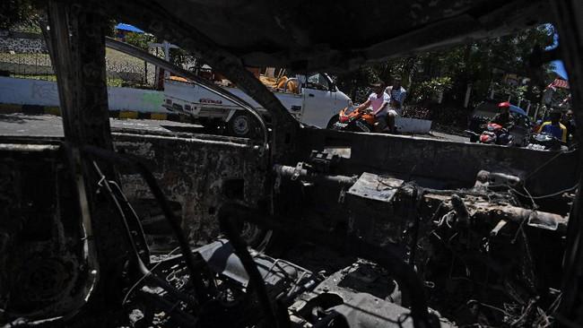 Pengendara melintas di samping bangkai mobil yang hangus terbakar di Jayapura, Papua, Sabtu (31/8). Saat kerusuhan terjadi, beberapa bangunan dan kendaraan memang sempat dibakar massa yang mengamuk. (ANTARA FOTO/Zabur Karuru)