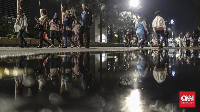 Sejumlah warga mengikuti pawai obor elektrik dalam rangka memeriahkan Jakarta Muharam Festival 2019. (CNN Indonesia/Bisma Septalisma)
