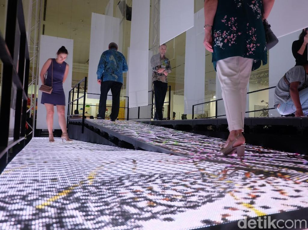 Salah satu instalasi interaktif lainnya adalah karya Isha Hening. Siapa pun boleh berjalan di atas lantai yang menimbulkan efek art video. Foto: Tia Agnes/detikHOT