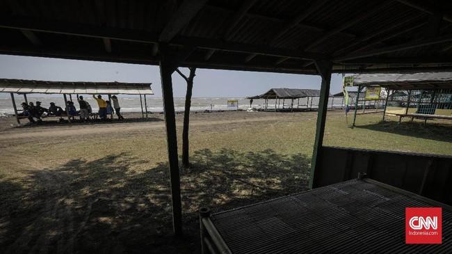 Kebocoran minyak itu membuat para nelayan juga beralih profesi menjadi pengumpul limbah. Di Pantai Pelangi para pengumpul limbah ini terlihat beristirahat ketika di tengah-tengah suasana sepi pantai yang ditinggal pengunjung, Selasa (20/8). (CNN Indonesia/Adhi Wicaksono)