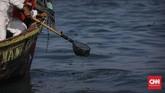 Para pengumpul limbah mengumpulkan gumpalan minyak menggunakan peralatan sederhana yaitu tongkat dan bambu. Setiap harinya satu kapal pengumpul limbah bisa mengambil hingga 80 karung limbah dari laut. (CNN Indonesia/Adhi Wicaksono)