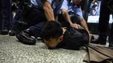 Sejumlah rekaman video yang tersebar di media sosial menunjukkan aparat kepolisian menangkap dan memukul kerumunan pedemo yang meringkuk di dalam gerbong kereta. (Philip FONG / AFP)