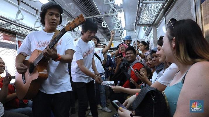 Aksi Band D'Masiv saat menghibur penumpang di dalam Kereta Rel Listrik di Jakarta, Senin (2/9/2019).  Band D'Masiv menghibur penumpang KRL dalam rangka merayakan Hari Pelanggan Nasional yang jatuh tiap tanggal 4 September. Grup band yang digawangi Rian ini menghibur pengguna jasa KRL dengan menyanyikan sejumlah lagu hits mereka. di Dalam KRL. Rian juga mengajakpara pengguna jasa untuk mencintai KRL Commuter Line dengan menjaga ketertiban dan kenyamanan bersama di kreta. (CNBC Indonesia/Muhammad Sabki)