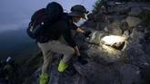 Tak hanya penduduk Jepang, turis mancanegara juga melakukan pendakian karena penasaran dengan panorama matahari terbit di Gunung Fuji. (AP Photo/Jae C. Hong)