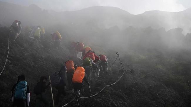 Berkabut dan licin adalah tantangan mendaki puncak Gunung Fuji untuk melihat pemandangan matahari terbit.(AP Photo/Jae C. Hong)