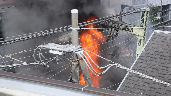 Api berkobar di lokasi tabrakan kereta dan truk di Yokohama. Sebanyak tiga dari delapan gerbong keluar jalur dalam kejadian itu. (TWITTER @TATSU_PHOTO/via REUTERS)
