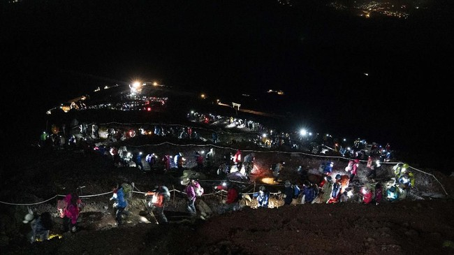 Pendakian ke puncak Gunug Fuji dilakukan pada dini hari. Malam sebelumnya, pendaki bermalam di tenda. (AP Photo/Jae C. Hong)