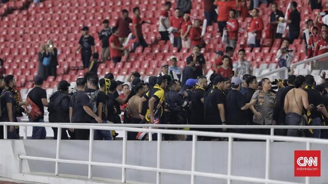 Suporter Malaysia terdesak di tribune Selatan usai mendapat lemparan botol dari suporter Indonesia. Mereka baru berhasil dievakuasi polisi pada dini hari. (CNNIndonesia/Adhi Wicaksono)