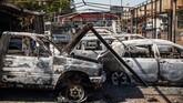 Mobil yang terbakar milik pemilik dealer mobil Afrika Selatan Yunus Salajee terlihat di Johannesburg pinggiran Malvern, (4/9). Setelah ibukota keuangan Afrika Selatan dilanda gelombang baru kekerasan anti-orang asing.(Michele Spatari / AFP)