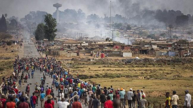 Massa yang dipersenjatai dengan tombak, pentungan dan kapak berjalan melalui Katlehong Johannesburg. Kejadian ini terjadi ketika gelombang kekerasan anti-asing, Kamis (5/9). (GUILLEM SARTORIO / AFP)