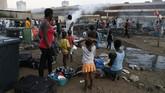 Warga negara asing duduk dan menyaksikan gubuk mereka dibakar oleh orang-orang yang diduga penjarah di Marabastad, dekat Distrik Pusat Bisnis Pretoria (CBD) di Pretoria, Afrika Selatan, (2/9). (Phill Magakoe / AFP)