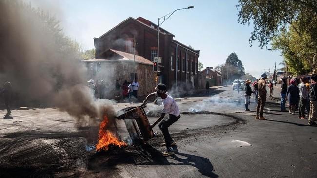 Seorang pria mengangkat perabot yang terbakar selama kerusuhan di pinggiran Turffontein, Johannesburg, (2/9). Saat itu, demonstran menjarah toko-toko milik asing dalam aksi yang menargetkan warga negara asing. (Michele Spatari / AFP)