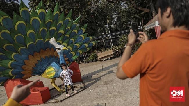 Pengunjung berfoto di pameran Flora dan Fauna 2019 di Lapangan Banteng, Jakarta, Minggu, 8 September 2019. (CNN Indonesia/Bisma Septalisma)