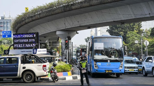 Polisi mengatur lalu lintas saat hari pertama penindakan sistem ganjil-genap di kawasan Matraman, Jakarta, Senin (9/9). (ANTARA FOTO/Galih Pradipta)
