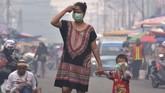 Seorang ibu dan anaknya mengenakan masker medis saat asap kebakaran hutan dan lahan (Karhutla) menyelimuti Kota Pekanbaru, Riau, Selasa (10/9/2019). ANTARA FOTO/FB Anggoro