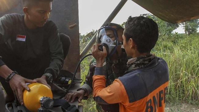 Petugas Badan Penanggulangan Bencana Daerah (BPBD) Pekanbaru memberikan bantuan oksigen kepada prajurit TNI dari Kodim 0301 Pekanbaru saat berupaya memadamkan kebakaran lahan gambut di Pekanbaru, Riau, Sabtu (7/9/2019). (ANTARA FOTO/Rony Muharrman)