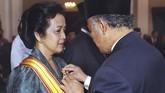 BJ Habibie menyematkan medali pada istrinya Hasri Ainun di IstanaNegara pada 14 Agustus. Kisah cinta Habibie dan istrinya sendiri sempat diabadikan menjadi film Habibie dan Ainun. Semasa hidupnya ia dikenal sangat menyayangi istrinya. (AFP PHOTO/AGUS LOLONG)