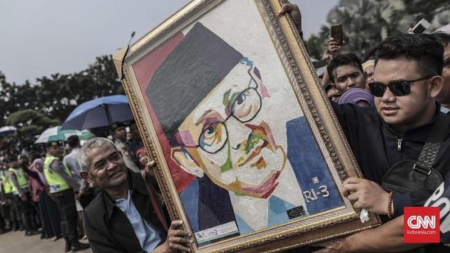 Sejumlah warga berdatangan untuk memberikan penghormatan terakhir kepada B.J. Habibie di Taman Makam Pahlawan Kalibata. Habibie juga dikenal aktif berorganisasi dan menjadi ketua pertama Ikatan Cendikiawan Muslim Indonesia (ICMI). (CNN Indonesia/Bisma Septalisma)
