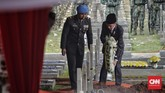 Presiden Joko Widodo (kanan) selaku Inspektur Upacara meletakkan karangan bunga di makam BJ Habibie. (CNN Indonesia/Adhi Wicaksono)