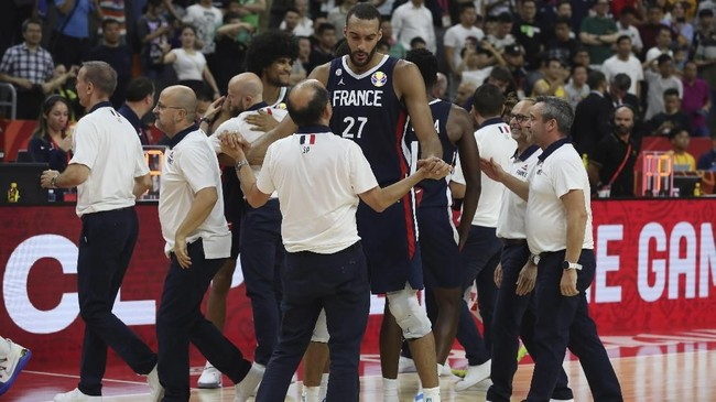 Center Prancis, Rudy Gobert, merayakan kemenangan atas Amerika Serikat bersama ofisial tim. Prancis lolos ke semifinal dan akan menghadapi Argentina yang di babak sebelumnya mengalahkan Serbia. (AP Photo/Ng Han Guan)