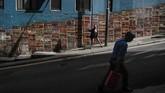 Seorang turis berpose untuk diambil gambarnya di depan mural karya seniman Alex Croft di distrik SoHo di Hong Kong. (AP Photo/Jae C. Hong)