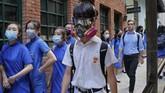 Para pelajar yang mengenakan masker bergandengan tangan mengelilingi Sekolah St. Stephen di Hong Kong. (AP Photo/Kin Cheung)