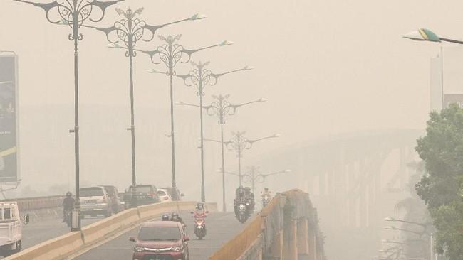 Pengendara menembus kabut asap dampak dari kebakaran hutan dan lahan di Pekanbaru, Riau, 12 September 2019. Kota Pekanbaru menjadi salah satu wilayah di Provinsi Riau yang terpapar kabut asap karhutla. (ANTARA FOTO/Rony Muharrman)