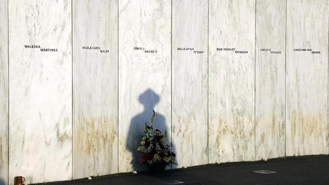 Tentara negara bagian Pennsylvania berhenti di depan tembok memorial di Shanksville, Philadelphia. Tembok itu didirikan untuk menghormati 40 orang yang tewas dalam pesawat 93 pada tragedi 9/11, 18 tahun yang lalu. (AP Photo/Gene J. Puskar)