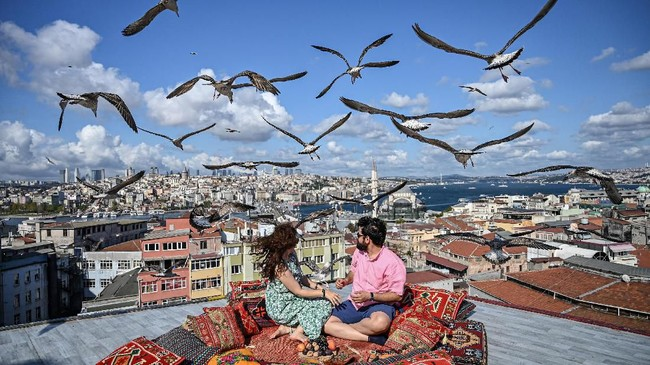 Sepasang kekasih duduk di teras suatu kafe di Istanbul sementara burung camar terbang di atas mereka. (Photo by Ozan KOSE / AFP)