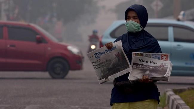 Seorang penjual koran mengenakan masker saat berjualan di tengah asap karhutla yang makin pekat menyelimuti Kota Pekanbaru, 13 September 2019. Pusat Pengendalian Pembangunan Ekoregion (P3E) Sumatera menyatakan Indeks Standar Pencemar Udara (ISPU) sebagian besar daerah di Riau dalam kategori berbahaya. (ANTARA FOTO/FB Anggoro)