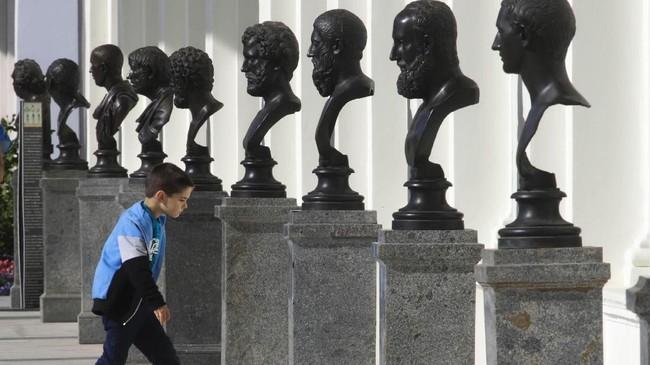 Seorang bocah berjalan melewati patung-patung di Galeri Cameron di Tsarskoe Selo di luar kota St. Petersburg, Rusia. (AP Photo/Dmitri Lovetsky)