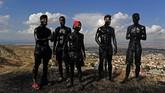 Remaja-remaja yang tubuhnya dilumuri oleh minyak hitam berdiri di atas bukit saat berlangsungnya festival tradisional Cascamorras di Baza, Spanyol. (AP Photo/Manu Fernandez)
