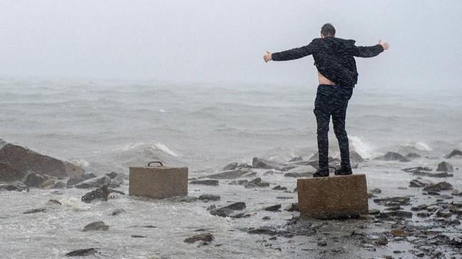 Pria yang tidak diketahui identitasnya mengangkat tangan ketika angin dari badai Dorian datang menghampiri pelabuhan Halifax di Dartmouth, Nova Scotia, Kanada. (Andrew Vaughan/The Canadian Press via AP)