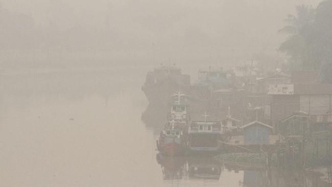Sejumlah kapal terparkir di pelabuhan rakyat sungai Siak ketika kabut asap pekat dampak dari kebakaran hutan dan lahan menyelimuti Kota Pekanbaru, Riau, 13 September 2019. (ANTARA FOTO/Rony Muharrman)