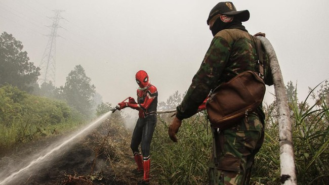 Seorang warga mengenakan kostum superhero membantu petugas BPBD Riau dan TNI Kodim 0313 Kampar saat memadamkan kebakaran lahan gambut di Rimbo Panjang, Kabupaten Kampar, Riau, 12 September 2019. (ANTARA FOTO/Rony Muharrman)