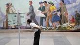 Seorang pria membaca koran di stasiun bawah tanah di Pyongyang, Korea Utara. (AP Photo/Dita Alangkara)