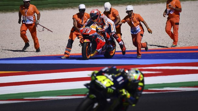 Valentino Rossi melintas dengan latar belakang Marc Marquez mengalami kecelakaan pada latihan bebas jelang babak kualifikasi MotoGP San Marino 2019. (Marco Bertorello / AFP)
