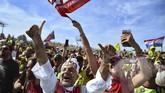 Sejumlah fan Marc Marquez merayakan kemenangan pebalap idolanya di antara para pendukung Valentino Rossi di MotoGP San Marino. (Photo by Marco BERTORELLO / AFP)