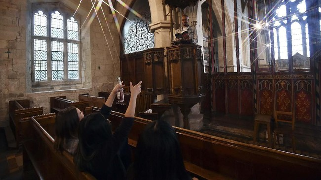 Guest Ismail Abdirahman (top) reads to his friends Andrea Stewart, Lingbo Zhou and Kae Ono from the pulpit at St Mary's Church, where guests can pay to stay overnight in what is known as 'champing', in Edlesborough, Buckinghamshire on September 2, 2019. (GLYN KIRK / AFP)