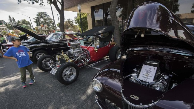 Seorang pengunjung menikmati deretan mobil klasik di 'Cruz'n for Roses' Hot Rod and Classic Car Show berlangsung di Pasadena, California. (Photo by Mark RALSTON / AFP)