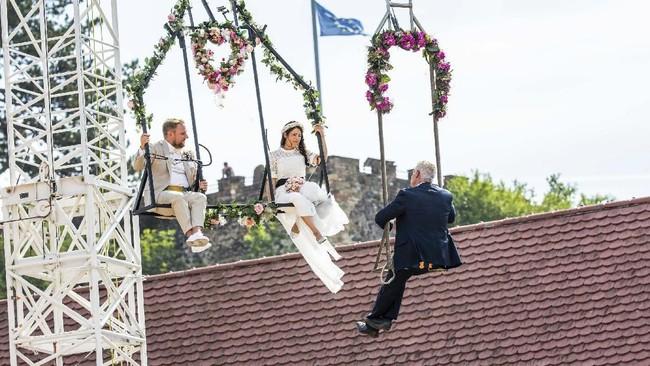 Dari kiri ke kanan, pengantin Sven Lier dan Anna Traber dan Wali Kota Breisach, Oliver Rein, dalam upacara pernikahan sambil 'melayang' di udara di Breisach, Jerman. (Philipp von Ditfurth/dpa via AP)