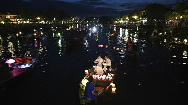 Orang-orang melepaskan lentera kertas dari atas perahu dalam festival di sungai Thu Bon, di Hoi An, situs UNESCO, Vietnam. (AFP/Manan Vatsyayana)