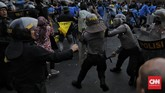Inisiatif polisi memadamkan api mendapat respons dari mahasiswa. Sebagian menolak polisi memadamkan api sehingga sempat terjadi bentrokan antara massa dan polisi. (CNN Indonesia / Adhi Wicaksono).