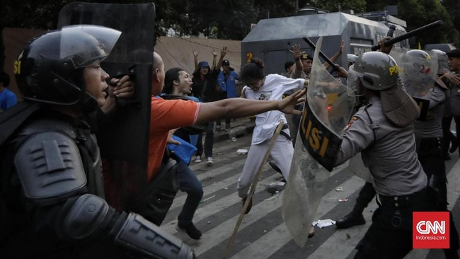 Polisi berusaha menghalau massa aksi untuk mencegah kericuhan meluas dan tidak terkendali. Demo massa PMII di Gedung Merah Putih KPK berjalan sejak siang, selepas salat Jumat. (CNN Indonesia / Adhi Wicaksono).