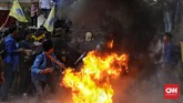Tak puas melempar telur, massa dari PMII membakar ban bekas di depan Gedung Merah Putih. Api berkobar cukup besar. Polisi bereaksi dengan mendatangi lokasi ban terbakar untuk memadamkan api. (CNN Indonesia / Adhi Wicaksono).